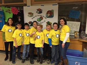 DI team standing in front of a project presentation in yellow shirts with team logo